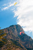 Parachute soaring in the clouds on a background of sky and mountains Stock Image