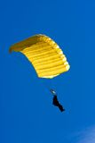 Parachuter. Descending with a yellow parachute against blue sky Royalty Free Stock Images