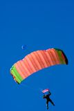 Parachuter. Descending with a red parachute against blue sky Stock Photo