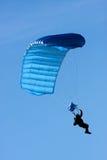 Parachuter. Descending with a blue parachute against blue sky Stock Photo