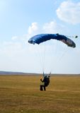 Parachuter. The man ready for landing with parachute Royalty Free Stock Image