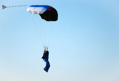 Parachuter. The man ready for landing with parachute Stock Photography