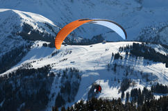 Parachuter above the snowy slope in the Alps. Parachutist is flying above snow-covered slopes at the Chamonix ski resort in the winter Alps Stock Photography