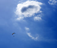 Parachuter in the air. Parachuter flying below a small cloud Stock Images