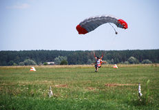 Parachuter alighting on the field. Parachutist is landing on the green field Royalty Free Stock Images