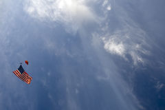 Parachuter with American Flag. A parachuter sails through the sky with the American Flag underneath Stock Photo