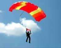 Parachuter avec un parachute jaune-rouge Photographie stock