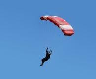 Parachuter in the blue sky. Parachutist with red parachute is flying in the blue sky Royalty Free Stock Photos