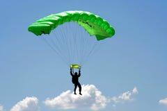 Parachuter and cloud. Parachuter  with green parachute on sky background Stock Photos