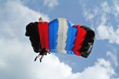 Parachuter con el paracaídas blanco azul rojo negro en la taza que se lanza en paracaídas imágenes de archivo libres de regalías