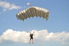 Parachuter con el paracaídas gris en la taza que se lanza en paracaídas vista de la parte posterior imágenes de archivo libres de regalías