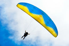 Parachuter descending with instructor. Against blue sky Royalty Free Stock Photo