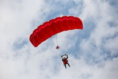 Parachuter descending with a red parachute. Against blue sky Royalty Free Stock Image
