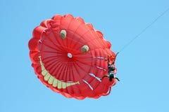The parachuter flies headfirst. The parachuter flies on a red parachute headfirst Stock Photo