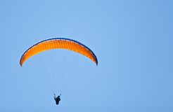 Parachuter in sky. Parachuter flying in air with blue sky Stock Photos