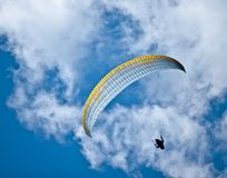 Parachuter in sky. Parachuter flying in air with blue sky and clouds Royalty Free Stock Images