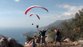 Parachutes paragliding overhead of tourists