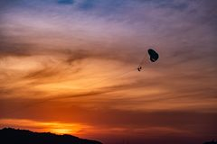 Parachutes in the seaside sunset stock image