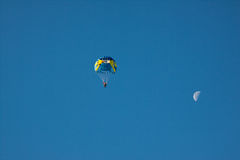 Parachutez sur le ciel bleu de fond et la lune Photographie stock