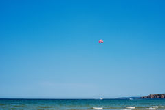 Parachuting over a sea, towing by a boat. Paragliding in the clear sky above the sea. Riding on a parachute behind a boat. Royalty Free Stock Images