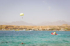 Parachuting over a sea, towing by a boat in Sharm El Sheikh Stock Photos