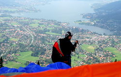 Parachuting. A parachuter is getting ready for his jump from Wallenberg, high above Tegernsee. Lake Tegern (Tegernsee), Bavaria, from Wallenberg with Rottach Stock Photos