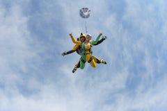 Parachutisme tandem Une fille active vole dans le ciel bleu photo stock