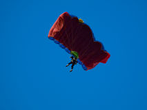 Parachutist. Colorful parachute against blue sky Stock Image