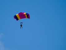 Parachutist. Colorful parachute against blue sky Royalty Free Stock Image