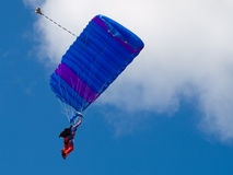 Parachutist. Colorful parachute against blue sky and white feathery clouds Royalty Free Stock Photography