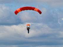 Parachutist. Colorful parachute against blue sky and white feathery clouds Royalty Free Stock Photo