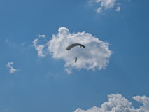 Parachutist. Silhouette of skydiver on blue sky with clouds on background Stock Photos