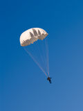 Parachutist,. Paratrooper with white parachute on blue sky Royalty Free Stock Image
