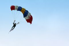 Parachutist Approaching. A skydiver parachuting down from the sky Stock Photos