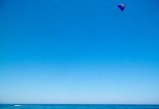 Parachutist in the blue sky above the blue sea. The parachutist flies high in the sky above the blue sea Royalty Free Stock Photography