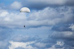 Parachutist descending from above with a white canopy. Parachutist descending from above with a white round canopy Royalty Free Stock Photography