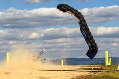 Parachutist die op het zand landen Stock Foto