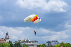 Parachutist in flight over buildings Stock Photo