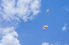 Parachutist in the sky. Two parachute jumpers with colorful parachutes on blue sky at the Red Bull Ordinul Smaranda competition on June 7, 2014 in Bucharest Royalty Free Stock Image