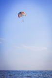 Parachutist flying on multi-colored parachute Royalty Free Stock Images