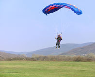 Parachutist landing. On a field after good flight Royalty Free Stock Photos