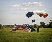Parachutist landing on field. A parachutist landing on a green field and a big American flag waving in the wind at an airshow at Virginia Beach, Virginia Royalty Free Stock Image