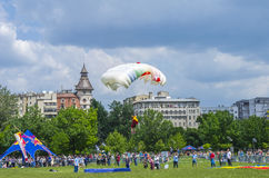 Parachutist landing. Parachute jumper landing on air mattress on field surrounded by people in the city at the Red Bull Ordinul Smaranda competition on June 7 Royalty Free Stock Photography