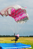 Parachutist landing under a pink parachute Royalty Free Stock Images