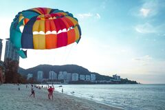 Parachutist lands on beach Stock Photo