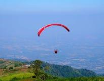 Parachutist met een rood valscherm Stock Fotografie