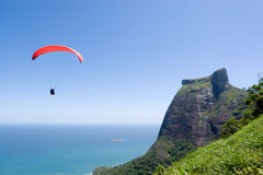 Parachutist over coast. Scenic view of parachutist over ocean coastline with blue sky background Royalty Free Stock Photo
