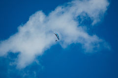 Parachutist. A photo of a parachutist in mid-air, gliding in front of a broken cloud Stock Photos