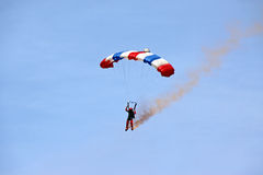 Parachutist / sky diver coming down to earth. Parachute / parachutist / sky diver against blue sky with smoke and colorful parachute coming down to land on earth Royalty Free Stock Photo