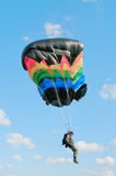 The parachutist under a multi-colour parachute Stock Images